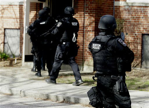 An official wearing tactical gear, right, looks on as others enter an apartment building in Watertown, Mass., Friday, April 19, 2013.   <span class=meta>(AP Photo&#47; Julio Cortez)</span>