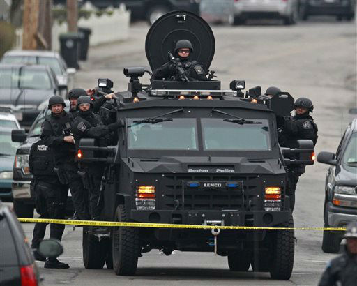 Police in tactical gear arrive on an armored police vehicle as they surround an apartment building while looking for a suspect in the Boston Marathon bombings in Watertown, Mass., Friday, April 19, 2013.  <span class=meta>(AP Photo&#47; Charles Krupa)</span>