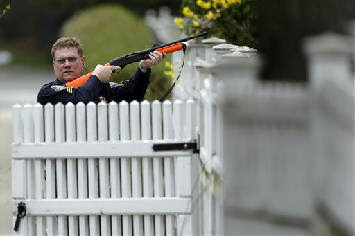 A police officer points his weapon at a residence as he conducts a search for a suspect in the Boston Marathon bombings, Friday, April 19, 2013, in Watertown, Mass.  <span class=meta>(AP Photo&#47; Matt Rourke)</span>