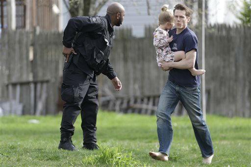 A police officer evacuates a shoeless man holding a child as members of law enforcement conduct a search for a suspect in the Boston Marathon bombings, Friday, April 19, 2013, in Watertown, Mass.   <span class=meta>(AP Photo&#47; Matt Rourke)</span>