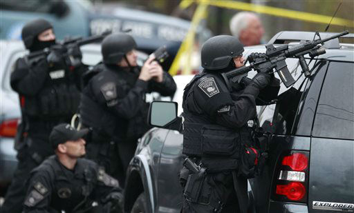 "<div class=""meta ""><span class=""caption-text "">Police in tactical gear surround an apartment building while looking for a suspect in the Boston Marathon bombings in Watertown, Mass., Friday, April 19, 2013.  (AP Photo/ Charles Krupa)</span></div>"
