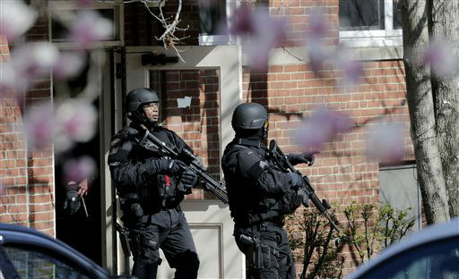 "<div class=""meta ""><span class=""caption-text "">Tactical teams exit an apartment building while searching for a suspect in the Boston Marathon bombings in Watertown, Mass., Friday, April 19, 2013.   (AP Photo/ Charles Krupa)</span></div>"
