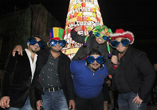 Iraqi tourists pose for a photograph in front of a Christmas tree as they celebrate the New Year during a countdown event in downtown Beirut, Lebanon, Tuesday, Jan. 1, 2013.  <span class=meta>(AP Photo&#47; Bilal Hussein)</span>