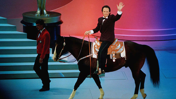 "<div class=""meta image-caption""><div class=""origin-logo origin-image ""><span></span></div><span class=""caption-text"">Those times when Billy Crystal wanted to be a memorable host...  In his second year as host, Crystal saluted Best Picture winner ""Dances with Wolves"" by riding off stage on a horse at the end of the show. The next year he started the show wearing a Hannibal Lecter mask.  Year: 1991 (Photo/Reed Saxon)</span></div>"