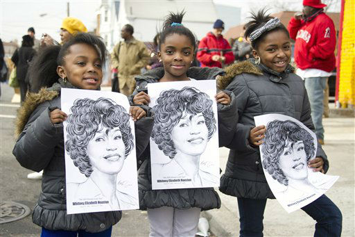 Fans hold pictures of Whitney Houston near the funeral services for the singer at the New Hope Baptist Church in Newark, N.J., Saturday, Feb. 18, 2012.  <span class=meta>(AP Photo&#47; Charles Sykes)</span>