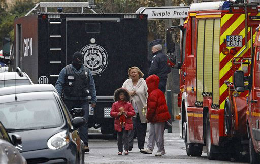 A woman and children are escorted by a police officer near a building where the chief suspect in an al-Qaida-linked killing spree was holed up in an apartment in Toulouse, France Thursday March 22, 2012.  <span class=meta>(AP Photo&#47; Remy de la Mauvinere)</span>