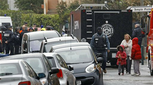 "<div class=""meta ""><span class=""caption-text "">A woman and children are escorted by a police officer near a building where the chief suspect in an al-Qaida-linked killing spree was holed up in an apartment in Toulouse, France Thursday March 22, 2012.  (AP Photo/ Remy de la Mauvinere)</span></div>"