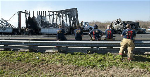 Firemen watch as cleanup crews work on vehicles that were involved in a multi-vehicle accident on Interstate 75 near Gainesville, Fla., Sunday, Jan. 29, 2012.  <span class=meta>(AP Photo&#47; Phil Sandlin)</span>