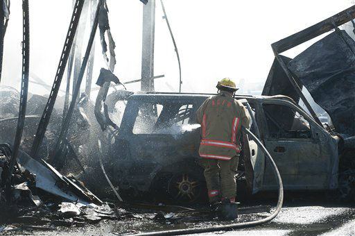 A fireman sprays the interior of a burned vehicle that was involved in a multi-vehicle accident on Interstate 75 near Gainesville, Fla., Sunday, Jan. 29, 2012.  <span class=meta>(AP Photo&#47; Phil Sandlin)</span>