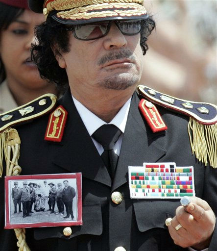 "<div class=""meta ""><span class=""caption-text "">In this Wednesday, June 10, 2009 file picture  Libyan leader Moammar Gadhafi walks past the honor guard with Italian Premier Silvio Berlusconi, unseen,  after landing at Rome's Ciampino airport. On his jacket he wears a photo showing Omar Mukhtar  (in chains) who organized and devised strategies for the Libyan resistance against the Italian colonization. He was arrested and subsequently executed by hanging in 1931 by the Italians.   (AP Photo/ RICCARDO DE LUCA)</span></div>"
