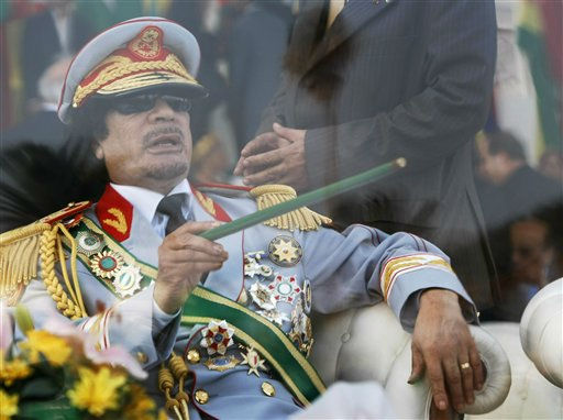 "<div class=""meta ""><span class=""caption-text "">In this Tuesday, Sept. 1, 2009 file photo, Libyan leader Moammar Gadhafi gestures with a green cane as he takes his seat behind bulletproof glass for a military parade in Green Square, Tripoli, Libya.  (AP Photo/ Ben Curtis)</span></div>"