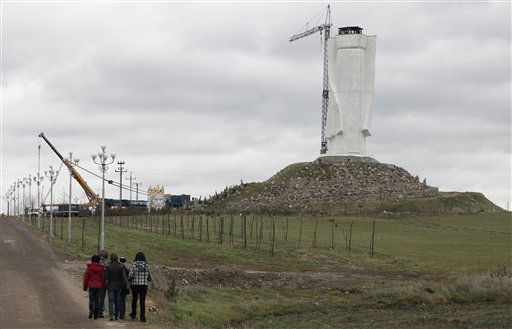 Strollers pass by as workers struggle against wind to assemble a crane to lift the 32-ton head and shoulders to top a giant concrete and metal statue of Jesus in Swiebodzin, western Poland, Friday, Nov.5, 2010.  <span class=meta>(AP Photo&#47; Czarek Sokolowski)</span>
