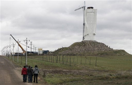 Strollers pass by as workers struggle against wind to assemble a crane that to lift the 32-ton head and shoulders to top a giant concrete and metal statue of Jesus in Swiebodzin, western Poland, Friday, Nov.5, 2010.  <span class=meta>(AP Photo&#47; Czarek Sokolowski)</span>