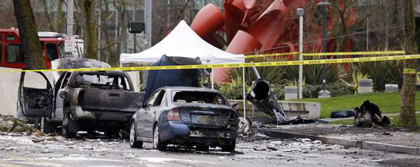 Burned vehicles are seen adjacent to the wreckage of a news helicopter, which crashed into a city street near the Space Needle, Tuesday, March 18, 2014, in Seattle. Two people were killed and another critically injured, according to the Seattle Fire Department.  <span class=meta>(AP&#47;Elaine Thompson)</span>