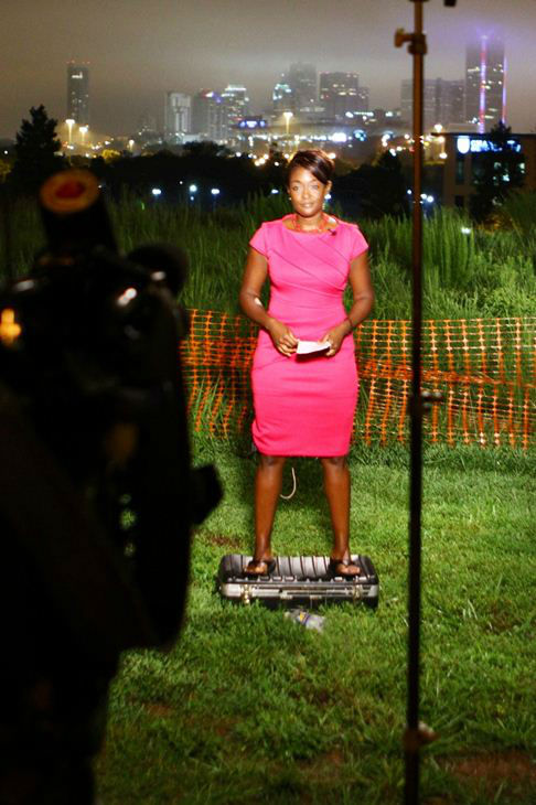 A &#34;height challenged&#34; Tamara Gibbs waits to go live standing on an equipment case so the Charlotte skyline shows up just right. <span class=meta>(WTVD Photo)</span>