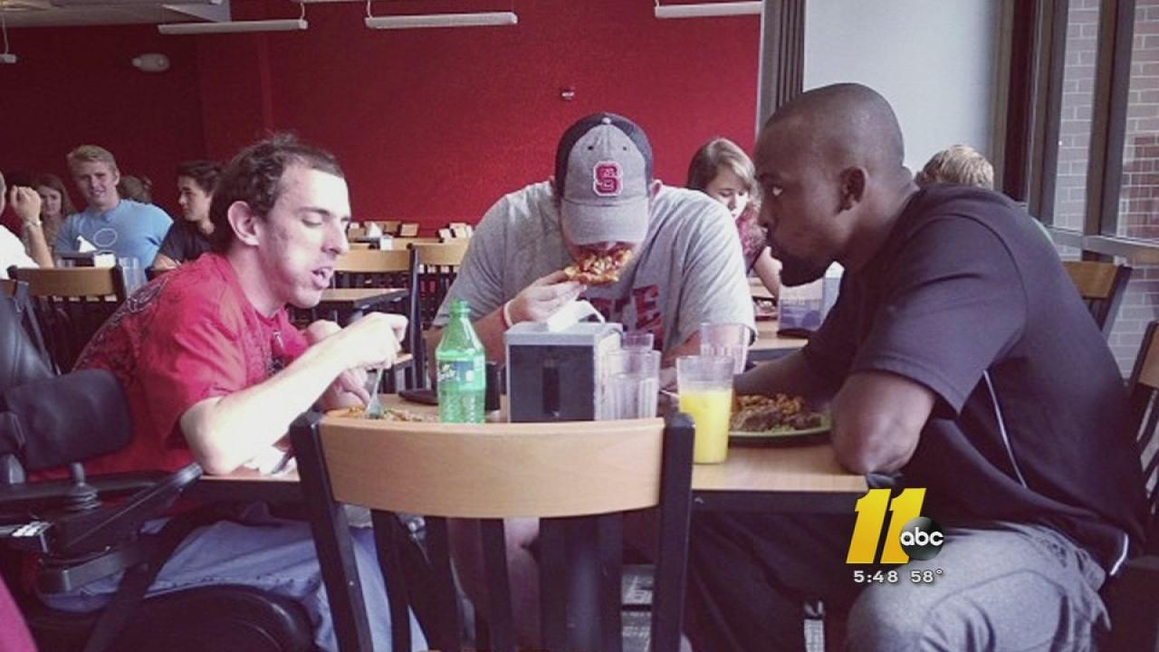 The photo shows student Will Spence (left) eating lunch with N.C. State football players Cole Blankenship (center) and Asa Watson (right).