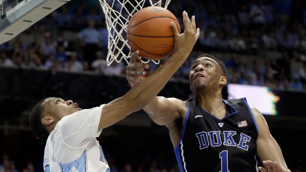 Duke's Jabari Parker (1) blocks North Carolina's Nate Britt during the first half of an NCAA college basketball game in Chapel Hill, N.C., Thursday, Feb. 20, 2014.