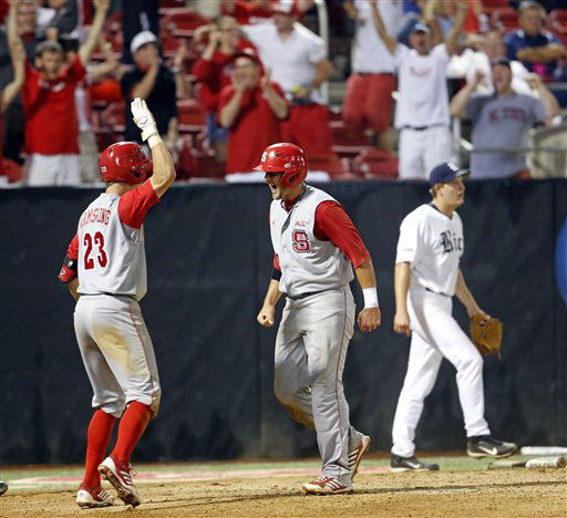 North Carolina State&#39;s Tarran Senay, center, celebrates scoring the go ahead run with teammate Jake Armstrong &#40;23&#41; with Rice pitcher John Simms nearby during the 17th inning of an NCAA college baseball tournament super regional game against Rice, Sunday, June 9, 2013, in Raleigh, N.C. North Carolina State won 5-4 in 17 innings. &#40;AP Photo&#47;Karl B DeBlaker&#41; <span class=meta>(AP Photo&#47; Karl B DeBlaker)</span>