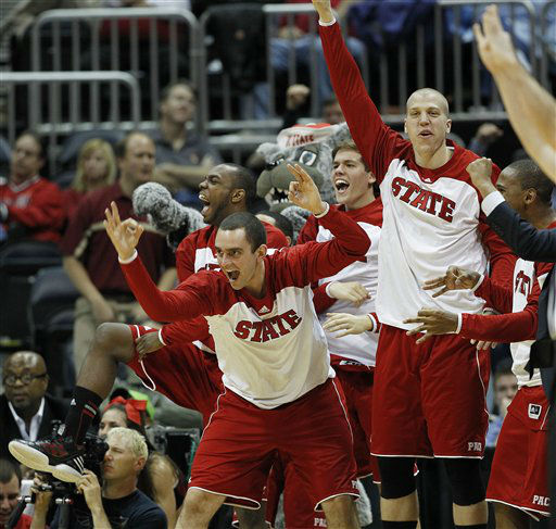 North Carolina State players react to a three-point shot made by North Carolina State guard Lorenzo Brown during the second half of an NCAA college basketball game against Virginia in the quarterfinals of the Atlantic Coast Conference tournament,  Friday, March 9, 2012, in Atlanta.  <span class=meta>(AP Photo&#47; John Bazemore)</span>