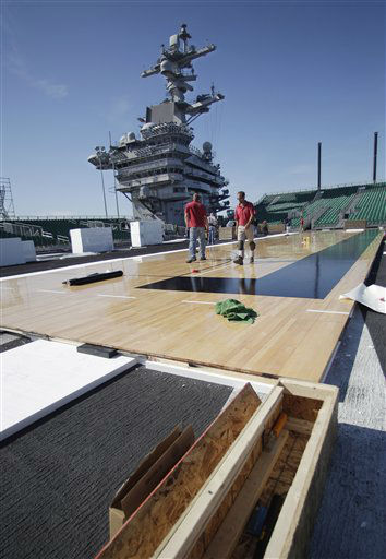 Workman install the basketball floor on the flight deck of the USS Carl Vinson in preparation of the Carrier Classic college basketball game Tuesday, Nov. 8, 2011 in Coronado, Calif.  North Carolina and  Michigan State will play in the first Carrier Classic on Friday Nov. 11.  <span class=meta>(AP Photo&#47; Lenny Ignelzi)</span>