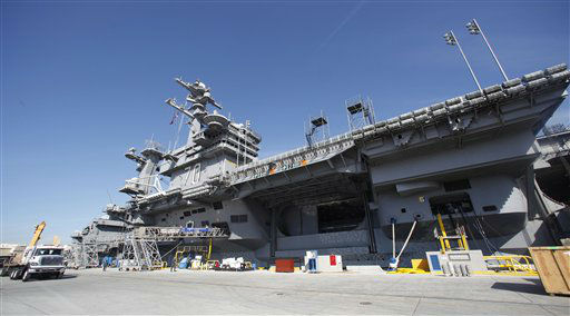 Light standards and camera platforms rise from the deck of the USS Carl Vinson at it&#39;s dock site in Coronado, Calif.  Tuesday, Nov. 8, 2011.  North Carolina and  Michigan State will play the first Carrier Classic basketball game on the flight deck of the ship.  <span class=meta>(AP Photo&#47; Lenny Ignelzi)</span>