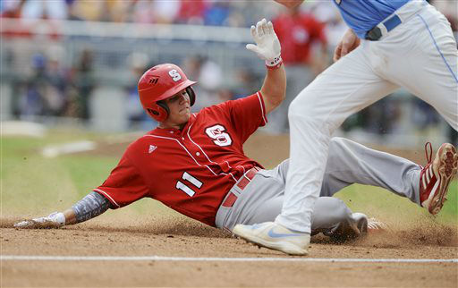 North Carolina State&#39;s Brett Austin &#40;11&#41; slides safely into third base against North Carolina third baseman Colin Moran on a fly ball by Tarran Senay in the third inning of an NCAA College World Series baseball game in Omaha, Neb., Sunday, June 16, 2013.  <span class=meta>(AP Photo&#47; Eric Francis)</span>