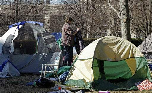 A man who gave his name only as Ron breaks down his tent near city offices in Charlotte, N.C., Monday, Jan. 30, 2012. Members of the Occupy Charlotte movement were ordered to remove their tents from the lawn of the old city hall Monday. (AP Photo/Chuck Burton)