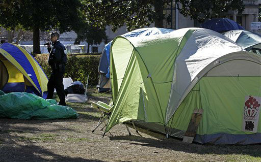 A Charlotte-Mecklenburg Police officer examines Occupy Charlotte tents in front of city offices in Charlotte, N.C., Monday, Jan. 30, 2012. Members of the Occupy Charlotte movement were ordered to remove their tents from the lawn of the old city hall Monday. (AP Photo/Chuck Burton)