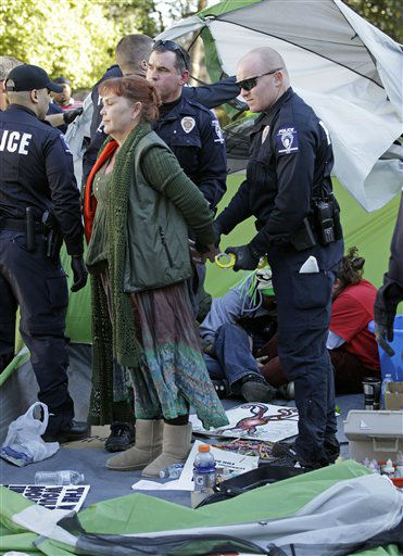 Charlotte-Mecklenburg Police arrest Laurel Green, of the Occupy Charlotte movement, as they remove tents belonging to the group from city-owned property in Charlotte, N.C., Monday, Jan. 30, 2012. (AP Photo/Chuck Burton)