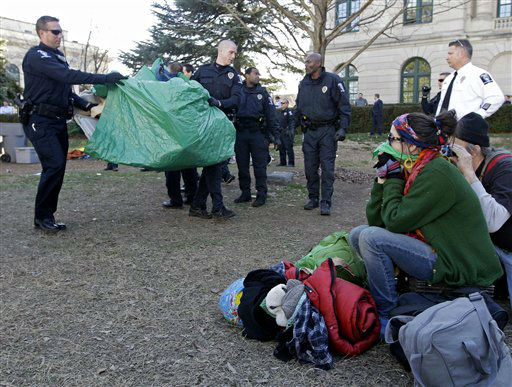 A woman who identified herself as Grammar Mars, right, looks on as Charlotte-Mecklenburg Police remove tents belonging to the Occupy Charlotte movement from city-owned property in Charlotte, N.C., Monday, Jan. 30, 2012. (AP Photo/Chuck Burton)