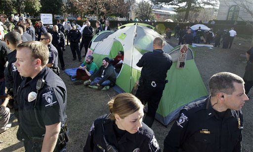 "<div class=""meta image-caption""><div class=""origin-logo origin-image ""><span></span></div><span class=""caption-text"">Charlotte-Mecklenburg Police surround a tent as they prepare to arrest members of the Occupy Charlotte movement as they remove tents belonging to the group from city-owned property in Charlotte, N.C., Monday, Jan. 30, 2012. (AP Photo/Chuck Burton)</span></div>"