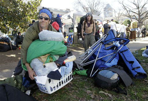 Peter Palumbo, left, removes his belongings before Charlotte-Mecklenburg police remove tents belonging to the group Occupy Charlotte from city-owned property in Charlotte, N.C., Monday, Jan. 30, 2012. (AP Photo/Chuck Burton)