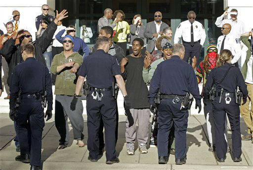 "<div class=""meta ""><span class=""caption-text "">Charlotte-Mecklenberg police move Occupy Charlotte protestors from the street in front of the police headquarters  in Charlotte, N.C., Monday, Jan. 30, 2012. (AP Photo/Chuck Burton)</span></div>"