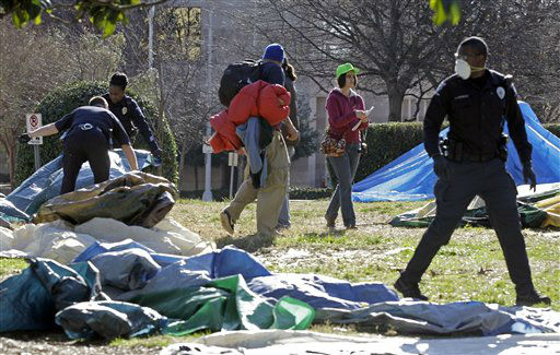 Charlotte-Mecklenburg Police remove tents belonging to the group Occupy Charlotte from city-owned property as members of the group look on in Charlotte, N.C., Monday, Jan. 30, 2012. (AP Photo/Chuck Burton)
