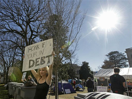 "<div class=""meta ""><span class=""caption-text "">Abigal Davis, of Occupy Charlotte, holds up a sign in Charlotte, N.C., Monday, Jan. 30, 2012. Charlotte-Mecklenburg police removed tents Monday belonging to the group from city-owned property. (AP Photo/Chuck Burton)</span></div>"