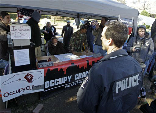 A Charlotte-Mecklenburg Police officer speaks to members of Occupy Charlotte in Charlotte, N.C., Monday, Jan. 30, 2012. Members of the Occupy Charlotte movement were ordered to remove their tents from the lawn of the old city hall Monday. (AP Photo/Chuck Burton)