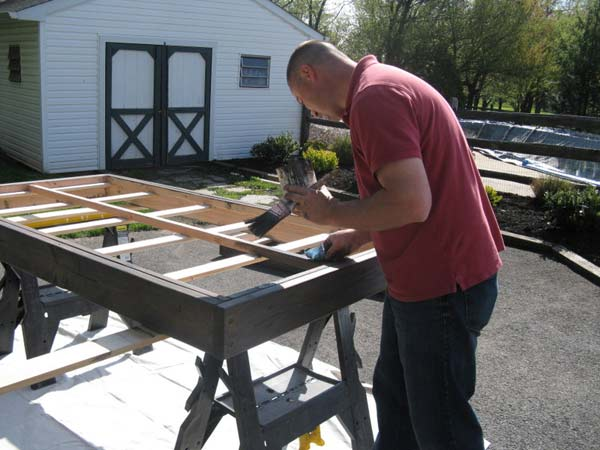 Homeowner Dave gets to work by staining the bunk...