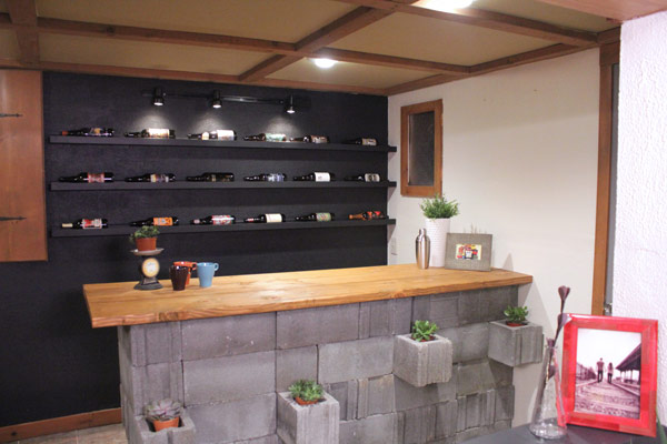 A concrete bar is really trendy and cool, but costs a bundle. Monica and Jess made their own out of cinderblocks and stained pine, even making room for some succulents to add a natural touch.