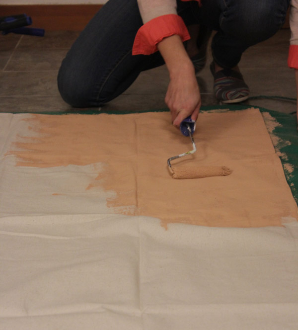 Using a roller, paint the drop cloth using your...
