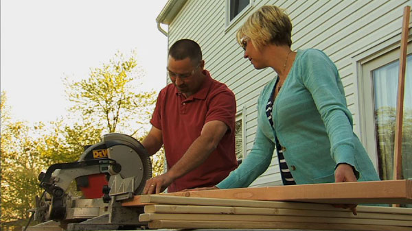 Monica and Dave start making the bunk beds by using a chop saw to cut 2 long boards and 4 small boards