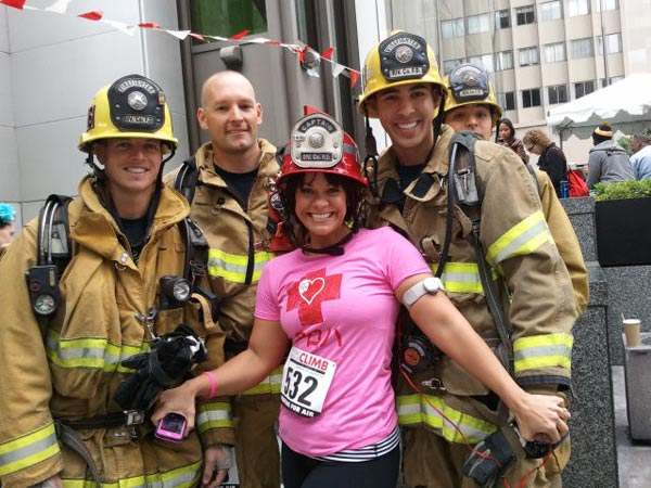 Ali Vincent poses with firefighters who are getting ready to complete in the Fight For Air Climb, a charity event where you race up 63 flights of stairs.